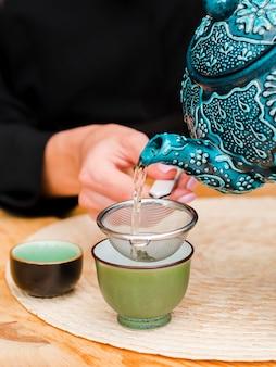 Frau, die tee in teetasse mit sieb gießt
