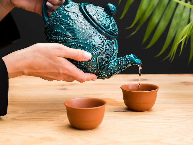 Frau, die tee in teetasse mit teekanne gießt