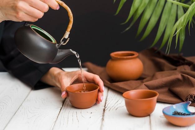 Frau, die tee in ton-teetasse gießt