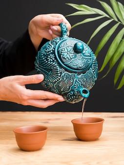 Frau, die tee in ton-teetasse mit teekanne gießt
