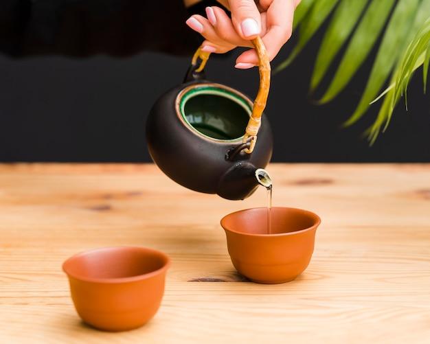 Frau, die tee in tonschale gießt