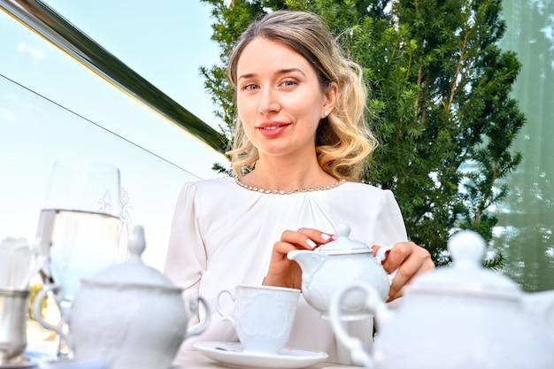 Frau, die tee oder kaffee in eine tasse gießt