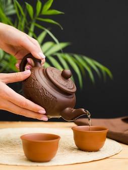 Frau, die tee von der teekanne in der teetasse gießt