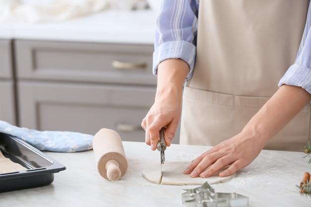 Frau, die teig auf tisch in der küche schneidet