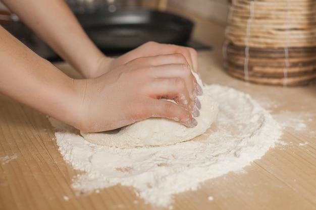 Frau, die teig macht. weibliche küche. chefkoch macht gebäck. nahaufnahmefrauenhände mit mehl und dem teig.