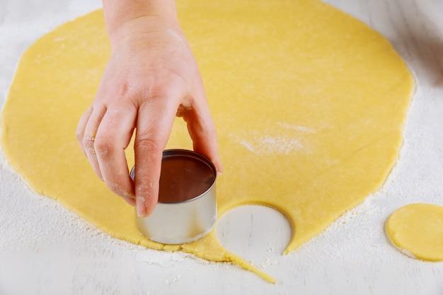 Frau, die teig schneidet, um kekse auf weißem tisch zu machen
