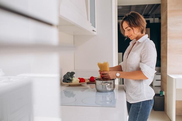 Frau, die teigwaren für abendessen an der küche macht