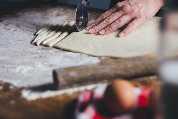 Frau, die teigwaren vom teig bildet