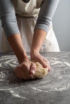 Frau, die teigwarenteig zubereitet