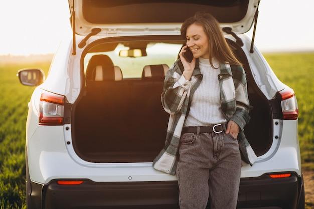 Frau, die telefon benutzt und durch das auto in einem feld steht