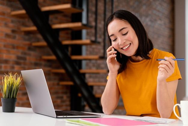 Frau, die telefon benutzt, während sie online-klasse besucht