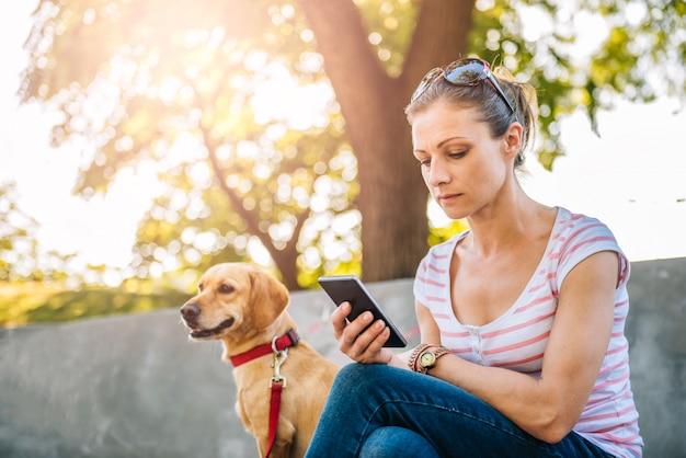 Frau, die telefon im park verwendet