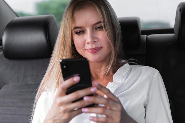 Frau, die telefon im rücksitz überprüft