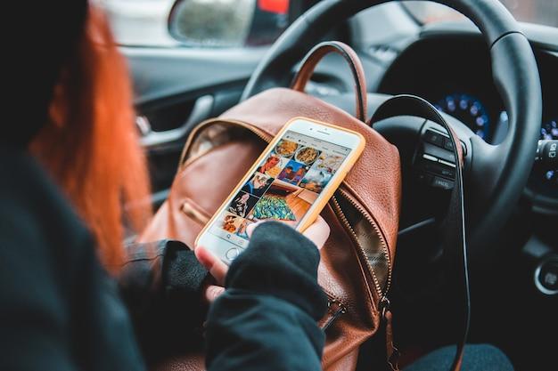 Frau, die telefon mit orange und schwarzem fall hält