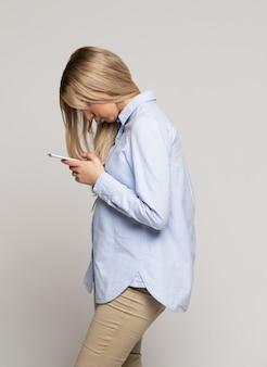 Frau, die telefon mit skoliose sucht und benutzt