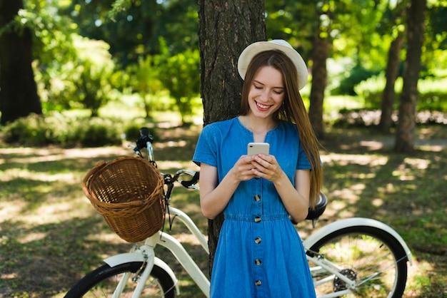 Frau, die telefon nahe bei fahrrad betrachtet
