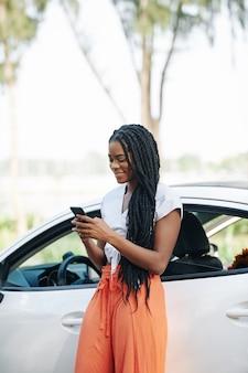 Frau, die telefon vor dem fahren überprüft
