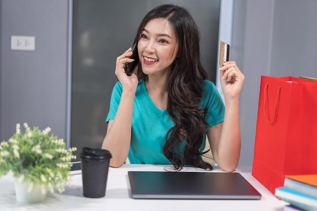 Frau, die telefonisch telefoniert und kreditkarte zum on-line-einkaufen hält