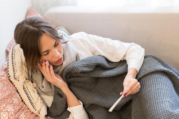 Frau, die temperatur mit digitalem thermometer nimmt und zum arzt ruft