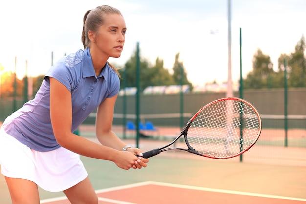 Frau, die tennis spielt und auf den service wartet.