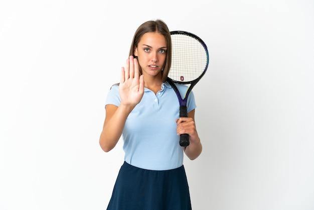 Frau, die tennis über isolierte weiße wand spielt, die stoppgeste macht