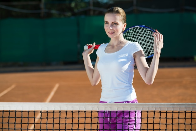 Frau, die tennisrakete auf der rückseite hält