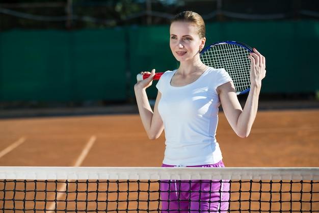 Frau, die tennisschläger auf der rückseite hält