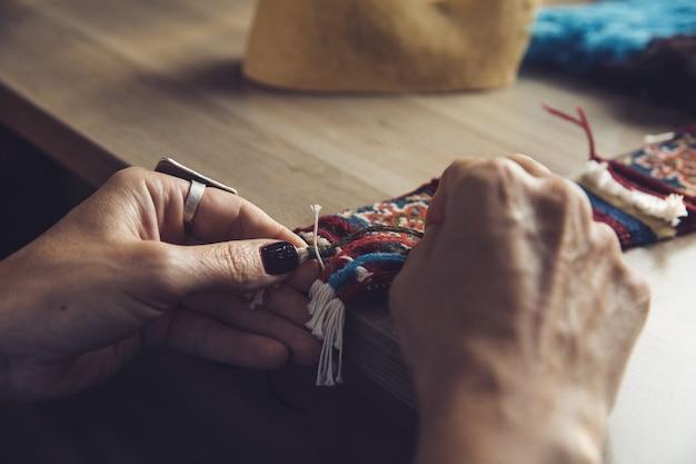 Frau, die teppich mit östlichen verzierungen strickt
