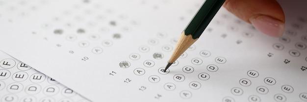 Frau, die tests löst und in bleistift auf papiernahaufnahme schreibt. prüfungstestkonzept