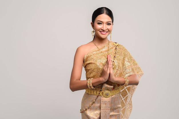 Frau, die thailändische kleidung trägt, die respekt zahlt