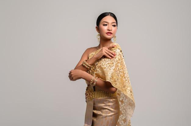 Frau, die thailändische kleidung und die rechte hand fasst ihre schultern trägt.