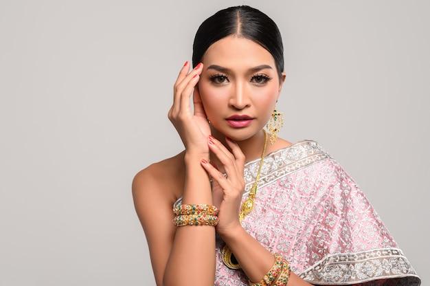 Frau, die thailändische kleidung und hände berühren den kopf trägt.