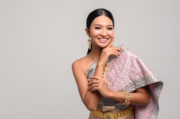 Frau, die thailändische kleidung und hände berühren ihr gesicht trägt