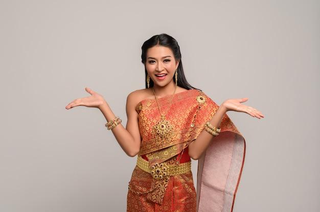 Frau, die thailändisches kleid trägt, das ein handsymbol machte