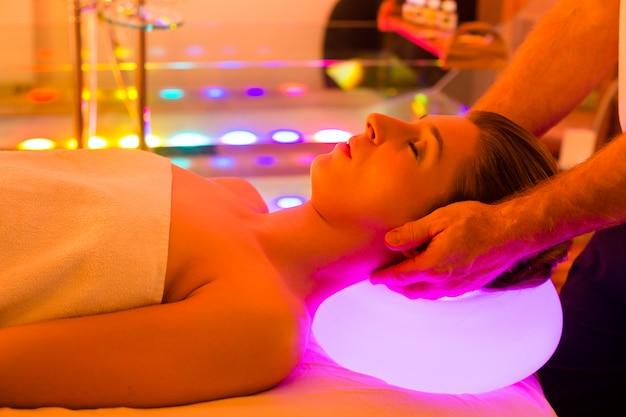 Frau, die therapie im badekurort mit farbtherapie genießt