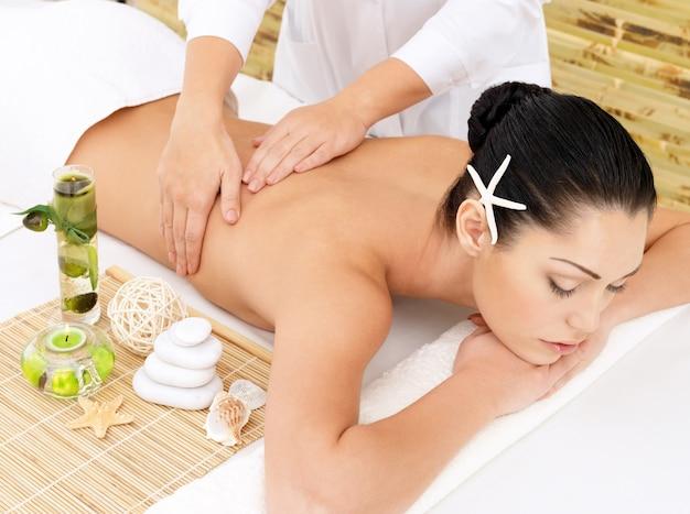 Frau, die therapiemassage des rückens im spa-salon hat. schönheitsbehandlungskonzept.