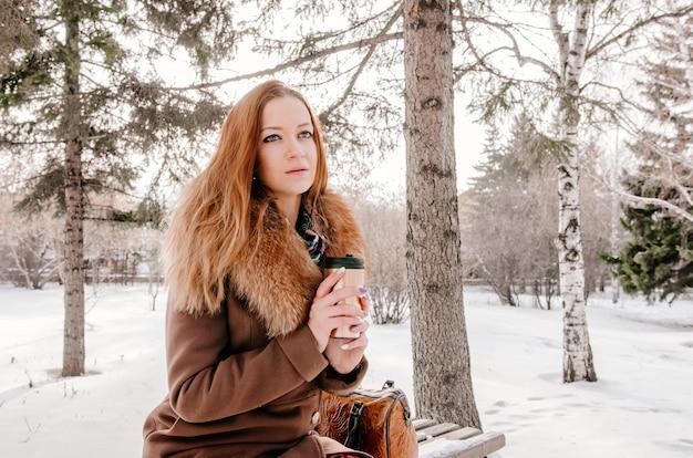 Frau, die thermischen becher im winterpark hält