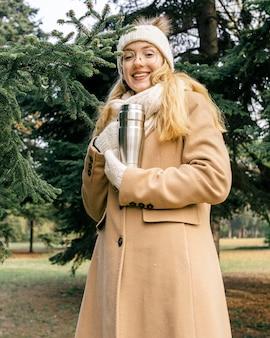 Frau, die thermosflasche am park im winter hält