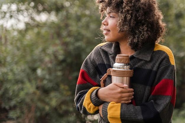Frau, die thermoskanne während des campings im freien mit kopienraum hält