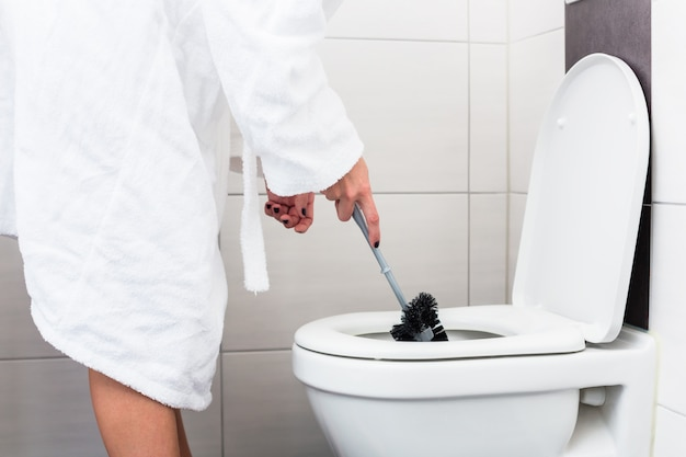 Frau, die toilette mit klobürste reinigt