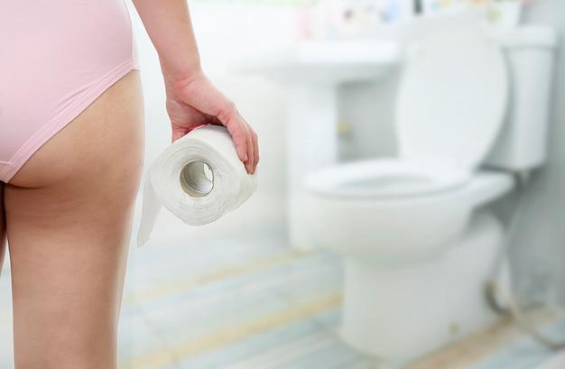 Frau, die toilettenpapier im badezimmer hält.