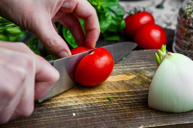 Frau, die tomate auf schneidebrett-nahaufnahme schneidet.