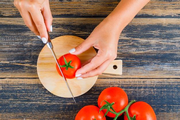 Frau, die tomate mit messer schneidet