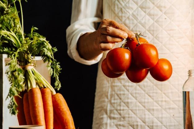 Frau, die tomaten und gemüse über einem tisch mit wasser nahe ihrem gesunden lebensmittelkonzept mit kopienraum hält