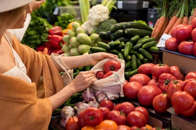 Frau, die tomaten vom marktplatz kauft