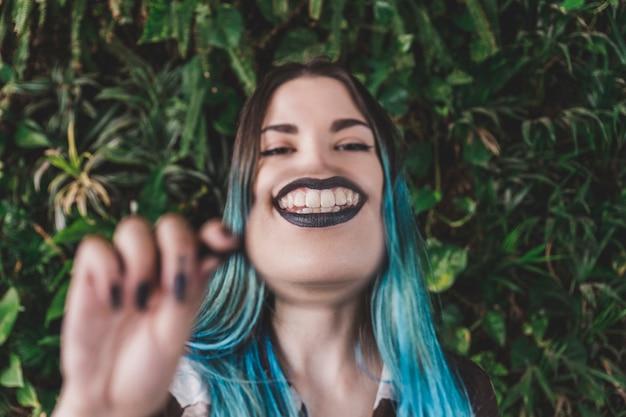Frau, die toothy lächeln durch ein vergrößerungsglas zeigt