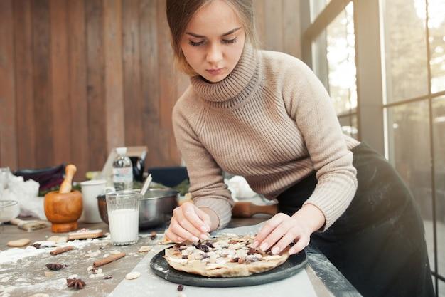 Frau, die torte mit getrockneten früchten verziert, auf hölzerner oberfläche