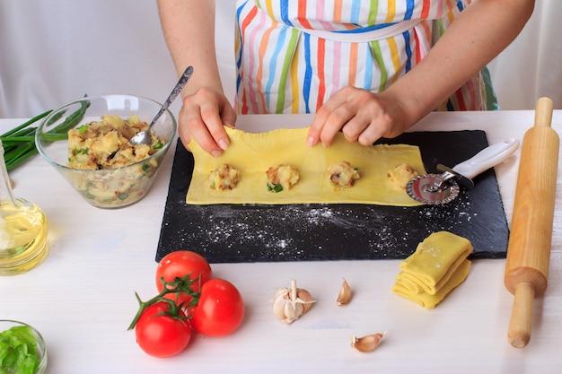 Frau, die traditionelle selbst gemachte italienische ravioli kocht