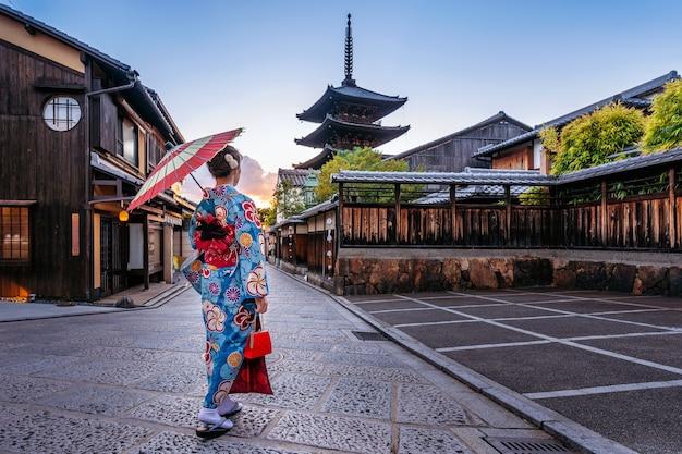 Frau, die traditionellen japanischen kimono mit regenschirm an der yasaka-pagode und an der sannen-zaka-straße in kyoto, japan trägt.
