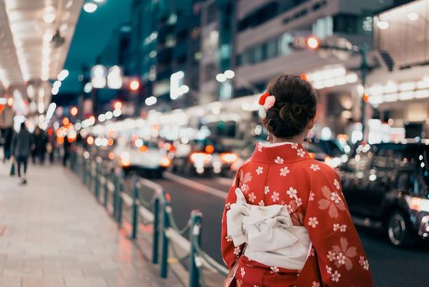 Frau, die traditionellen kimono auf einer straße in japan trägt